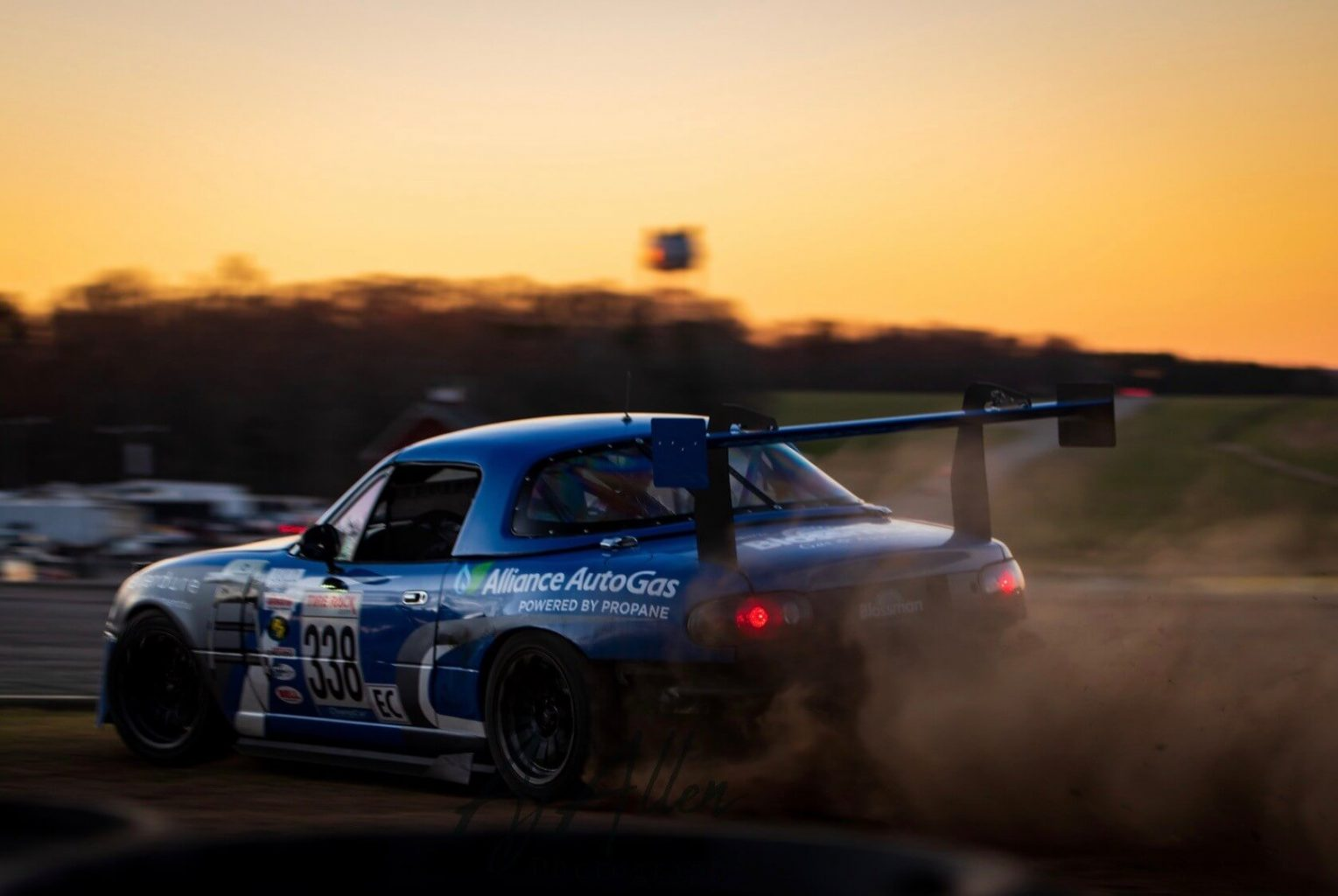 FiveTales Racing Blue Racecar on Track Racing During Sunset