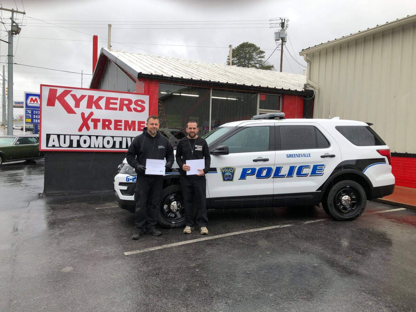 Kykers Xtreme Automotive newly trained propane autogas service techs pictured in front of propane autogas police vehicle
